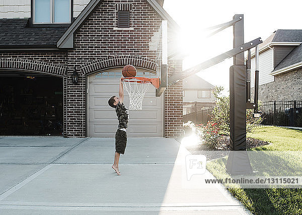 Side view of boy playing basketball in yard