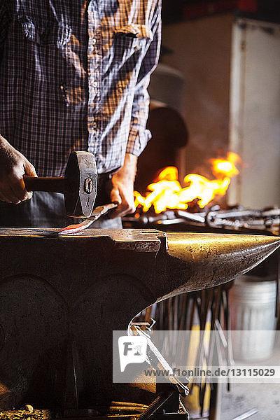 Beschnittenes Bild eines Handwerkers  der in der Fabrik auf Metall hämmert Beschnittenes Bild eines Handwerkers, der in der Fabrik auf Metall hämmert