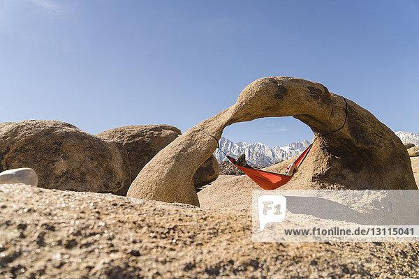 Frau entspannt sich auf Hängematte,  die an einer Felsformation vor klarem blauen Himmel hängt