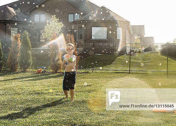 Boy squirting through water gun at backyard