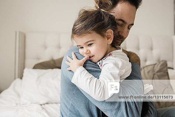 Loving father embracing daughter on bed at home
