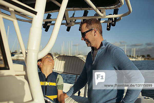 Happy father and son traveling in boat on sunny day