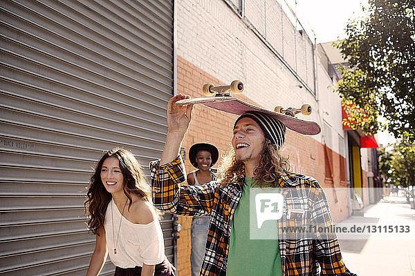 Mann trägt Skateboard auf dem Kopf  während er mit Freundinnen geht