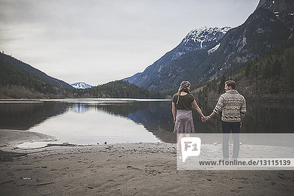 Rückansicht eines jungen Paares  das sich am Seeufer im Silver Lake Provincial Park an den Händen hält