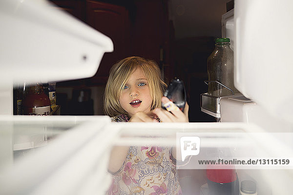 Cute girl looking into refrigerator at home