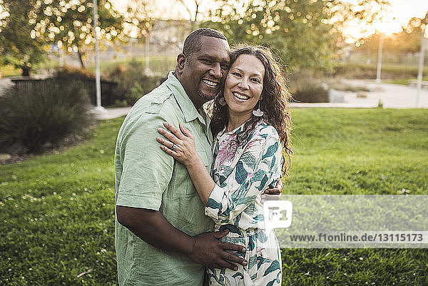 Portrait of smiling couple embracing on field at park