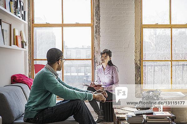Businesswoman talking to male coworker in office