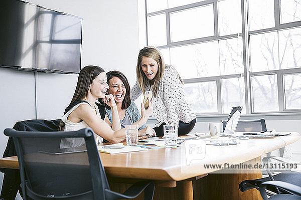 Glückliche Kolleginnen  die sich beim Sitzen im Sitzungssaal im Büro Selbsthilfe leisten