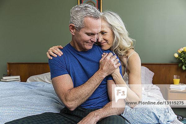 Liebender Mann hält die Hand der Frau  während er zu Hause auf dem Bett sitzt