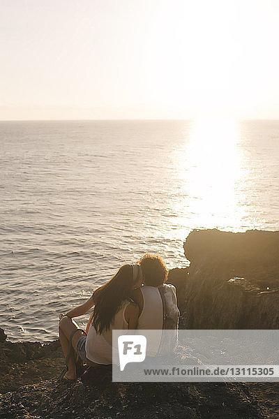 Rückansicht einer Freundin  die ihren Freund küsst  während sie bei Sonnenuntergang auf einem Felsen am Strand gegen den Himmel sitzt