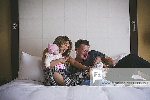 Glückliche Familie genießt zu Hause im Bett