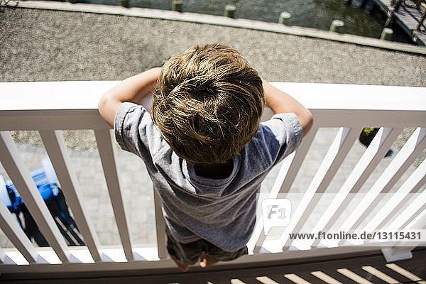 Hochwinkelaufnahme eines Jungen  der an einem sonnigen Tag am Geländer steht