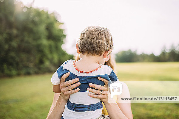 Mother lifting boy at park against sky