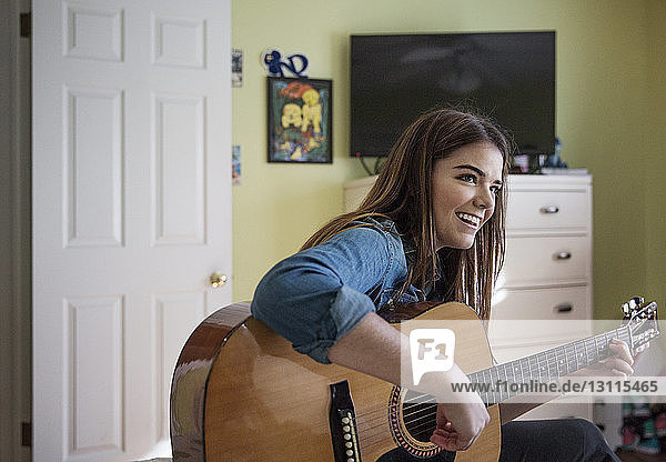 Happy woman playing guitar while sitting at home