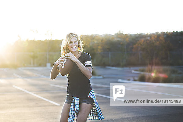 Fröhliche Frau spielt auf American-Football-Parkplatz