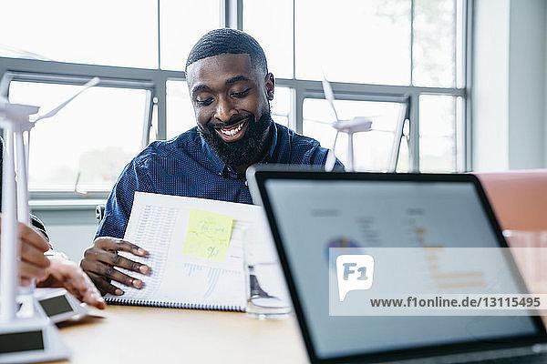Lächelnder Geschäftsmann liest Dokument  während er mit seinem Amtskollegen sitzt
