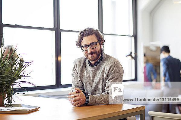 Porträt eines am Tisch sitzenden Geschäftsmannes mit einer Kollegin im Hintergrund im Büro