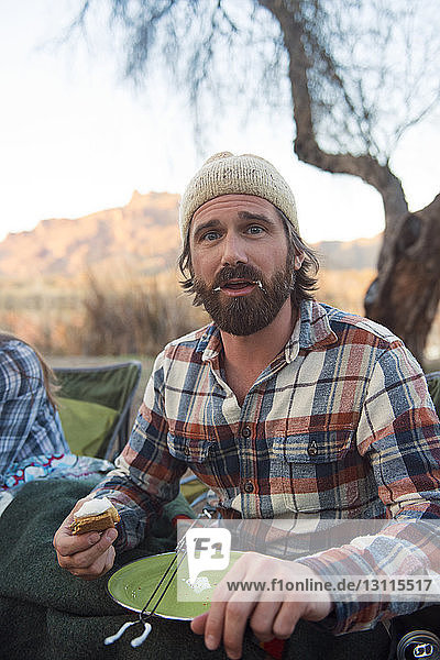Portrait of man with messy mouth holding s'more at camp site