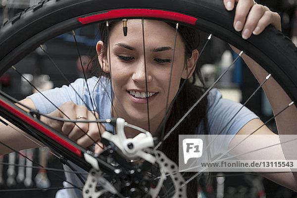 Frau stellt Fahrradrad in Werkstatt ein