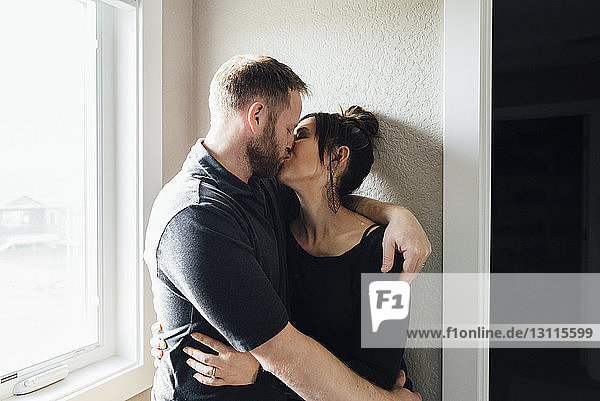 Affectionate Couple kissing while standing by window at home