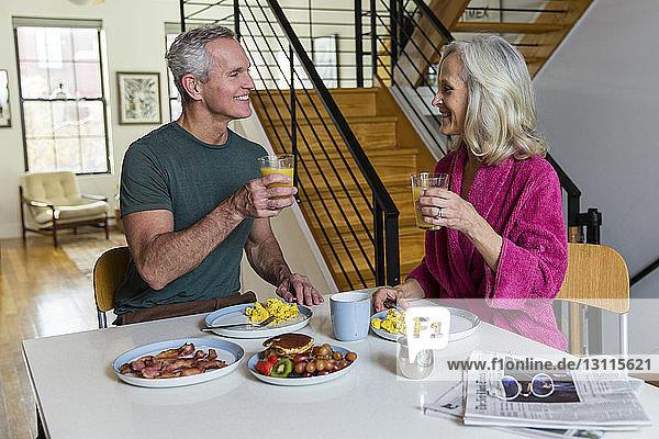 Lächelndes Paar hält Säfte in der Hand  während es sich am Esstisch von Angesicht zu Angesicht anschaut