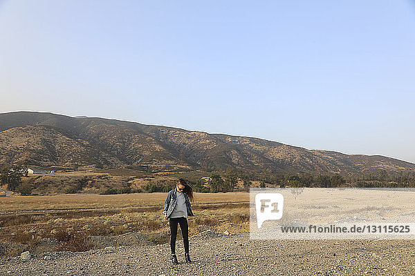 Full length of young woman standing against mountains and clear sky