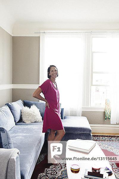Porträt einer lächelnden Frau mit Hand auf der Hüfte im heimischen Wohnzimmer stehend