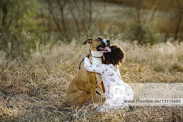 Seitenansicht eines Mädchens  das einen Hund umarmt  während es auf einem Grasfeld im Wald kniet