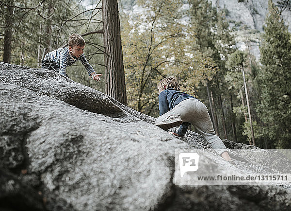 Brothers playing on rocks at Yosemite National Park