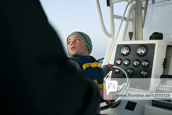 Boy looking over shoulder while holding steering wheel on boat