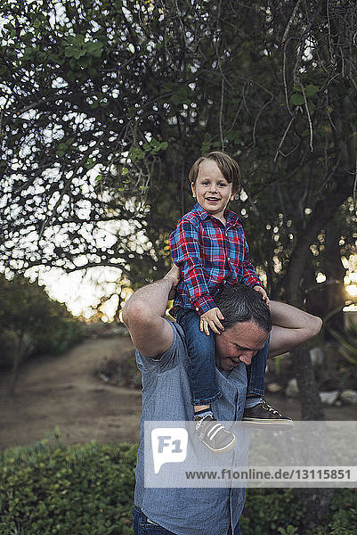 Portrait of smiling son sitting on father's shoulders while playing at park
