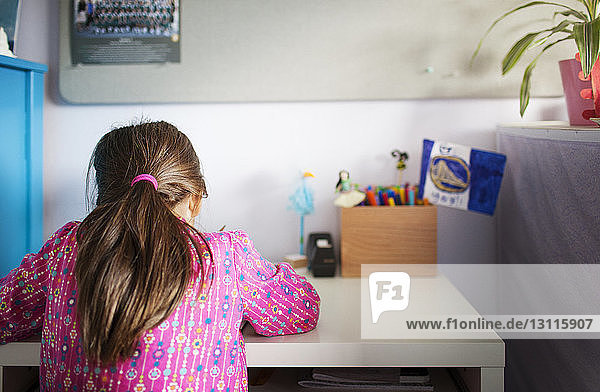 Rear view of girl studying at table