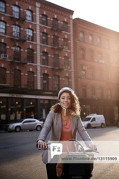 Glückliche Geschäftsfrau hält Fahrrad auf Straße