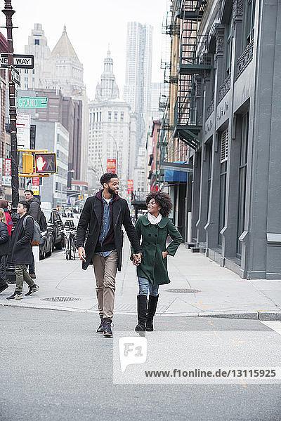 Geschäftspaar hält beim Überqueren einer Straße in der Stadt Händchen