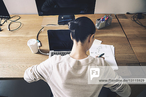 Overhead view of woman writing on paper while sitting at desk in office