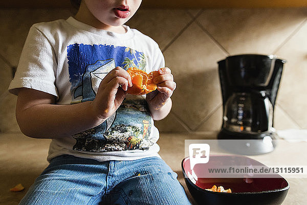 Midsection of boy peeling orange while sitting on kitchen counter