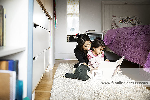 Mother teaching daughter while sitting on carpet in bedroom