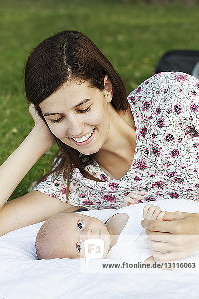 Close-up of mother lying with baby on grassy field at park