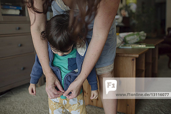 Midsection of mother dressing daughter while standing at home