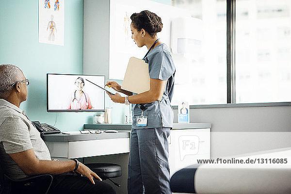Seitenansicht einer Ärztin  die in einer Telefonkonferenz mit einem Kollegen diskutiert  während der Patient in der Klinik sitzt