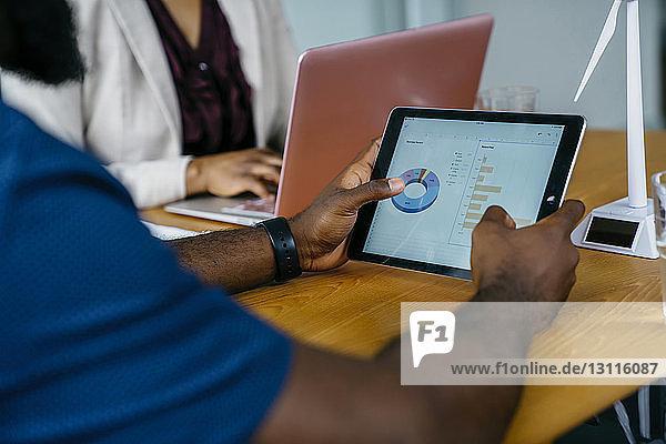 Mittelteil eines Geschäftsmannes  der einen Tablet-Computer benutzt  während er im Büro am Schreibtisch sitzt