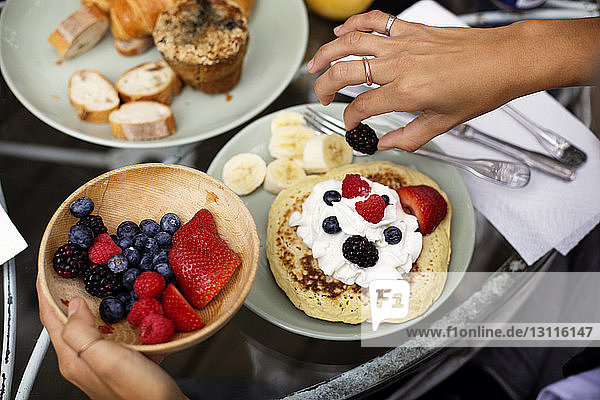 Cropped image of hands garnishing pancake with fruits and whipped cream on table