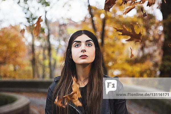 Nahaufnahme einer nachdenklichen Frau  die im Herbst auf einem Gehweg inmitten von Bäumen steht