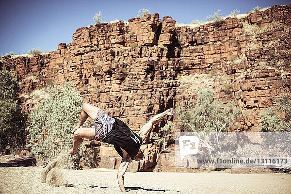 Mann tanzt auf Sand gegen Felsformationen in der Wüste