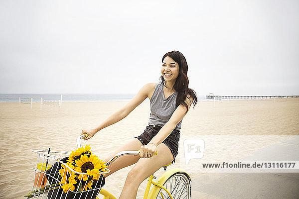 Fröhliche Frau radelt am Strand vor klarem Himmel
