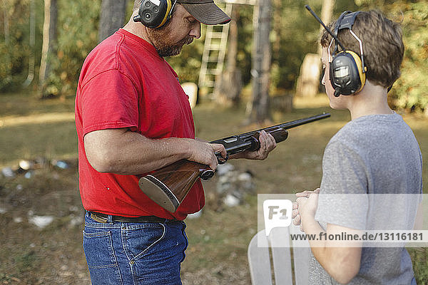 Son wearing headphones while looking at father adjusting rifle in backyard