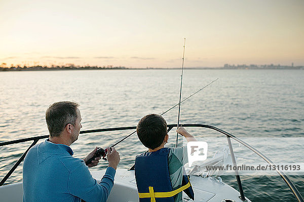 Father and son fishing on boat