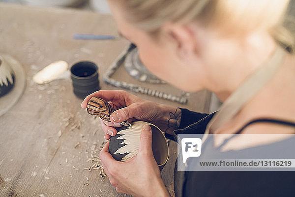 Hochwinkelansicht einer Frau  die am Tisch in der Werkstatt Keramik schnitzt Hochwinkelansicht einer Frau, die am Tisch in der Werkstatt Keramik schnitzt