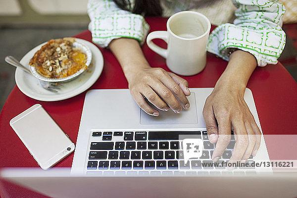 Draufsicht einer Frau mit Laptop am Tisch eines Straßencafés