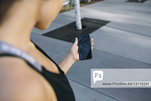 Cropped image of female athlete holding smart phone on footpath